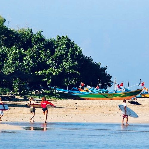 Groep surfers op het strand van Red Island