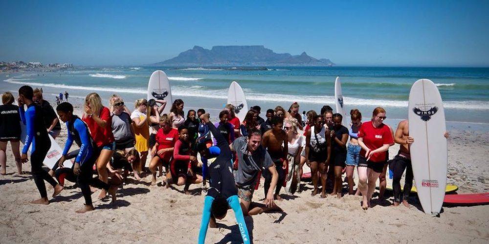 Met vrijwiligers en schoolkinderen het surfen leren in Kaapstad